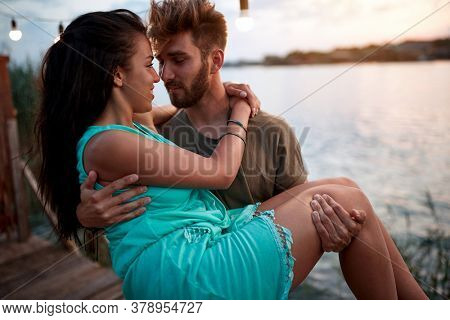 young beardy man holding in arms beautiful woman, by the sea at sunset. romantic couple in love
