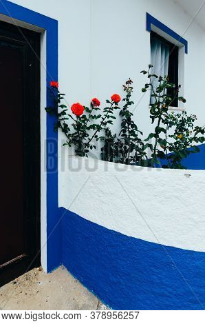 Red Roses On A Facade Of A Whitewashed Building In Porto Covo, Alentejo, Portugal