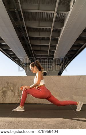 Fit Young Flexible Woman Doing Stretching Workout, Standing Under The Bridge. Fitness Model Doing Yo