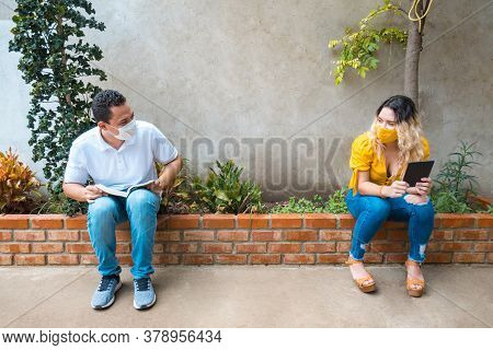 Young Latin Man And Woman Reading A Book And Wearing A Mask Sitting At A Distance. They Protect Them
