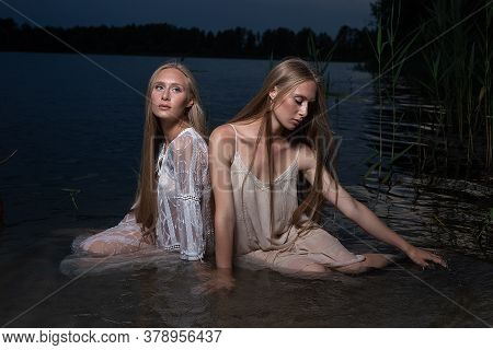 Two Attractive Young Twin Sisters With Long Blond Hair Posing In Light Dresses In Water Of Lake At S
