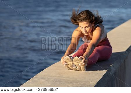 Young Yoga Runner Woman In Pink Legging Sitting On Embankment, Stretching Muscles In Seated Forward