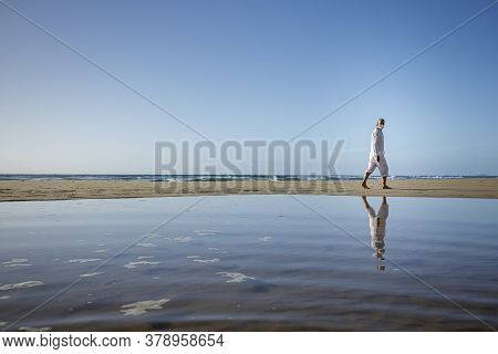 Man With Medical Mask Sitting On Beach During Coronavirus Covid 19 Pandemic, Social Distance Concept