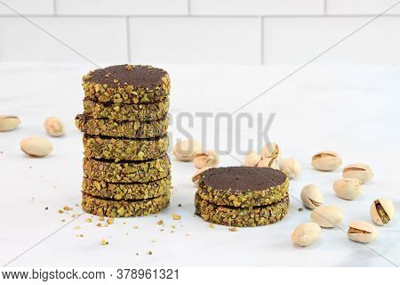 Stacked Chocolate Pistachio Cookies With Loose Whole Pistachios Around Them.  Macro.