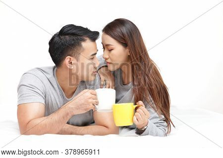 Lovers Lying On The Bed Holding A Cup Of Coffee Talk Happily In The Bedroom. White Background. The C