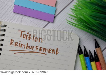 Tuition Reimbursement Text Write On A Book Isolated Wooden Table.
