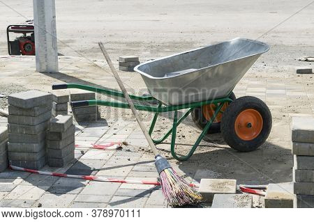 Metal Wheelbarrow And Paving Slabs. Construction Work On The Laying Of Paving Slabs In The City.