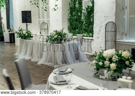 Presidium Of The Newlyweds At The Wedding. Focus On Table Setting In A Restaurant For A Holiday