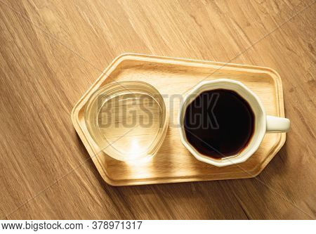 Top View Photo, A White Cup Of Americano Black Coffee And A Glass Of Mineral Water On Wooden Tray On