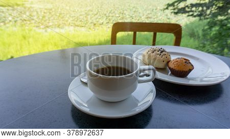 White Cup Of Americano Black Coffee, Cup Cake And Cereal Bread On White Plate On Black Table, Green