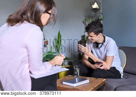 Teen Boy Talking To Professional Psychologist, Individual Therapy Session For Teenage With Doctor. D