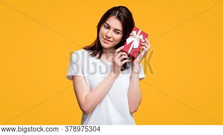 Birthday Surprise. Special Day. Curious Woman In White T-shirt Guessing Present In Gift Box Isolated