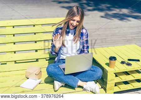 Woman With Headphones Having A Facetime Video Call With Laptop Outside. Happy And Smiling Girl Worki