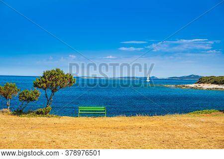 Beautiful Adriatic Shore In Croatia, Dugi Otok Island. Bench And Sailing Boat On Sea In Bay On Veli