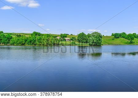 Beautiful Rural Panorama Of A Hilly Area With A House On The Other Side Of Pond (uhroidy/ugroedy Vil