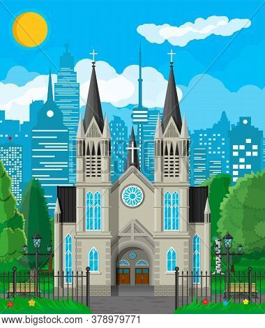 Exterior Of Catholic Or Protestant Church Cathedral In Gothic Style With Fence And Trees Behind. Cha