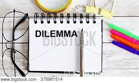 Dilemma Written In A Notebook On White Background With Office Tools
