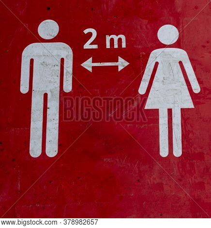 Red Sign On The Floor That Informs People To Keep 2 Meter A Social Distance.the Figures Of A Man And