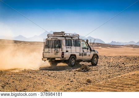 Hurghada, Egypt- Feb 4 , 2020:  Car or jeep offroad vehicle driving in desert sand dunes surface on blue sky background, safari and adventure, near Hurghada, Egypt.