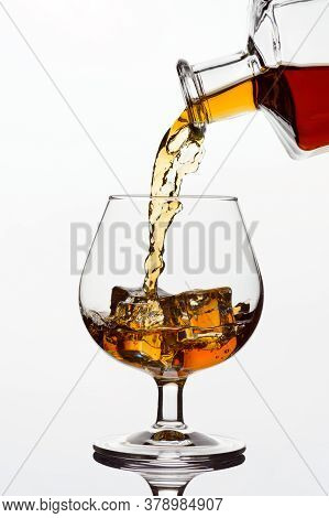 Whiskey Cognac Or Brandy Is Poured From A Transparent Bottle Into A Glass Glass With Ice, Freezing M