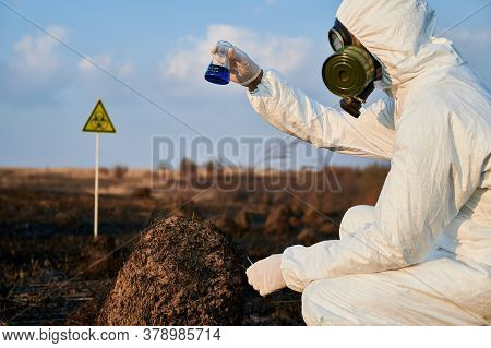 Ecologist In Suit, Gas Mask Holding Test Tube With Blue Liquid While Studying Burnt Grass And Soil O
