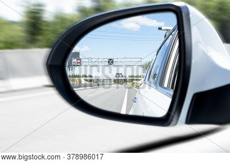 Cars Drive Along A High Road With Motion Blur Background. Car Side Mirror With Traffic. Car Rear Vie