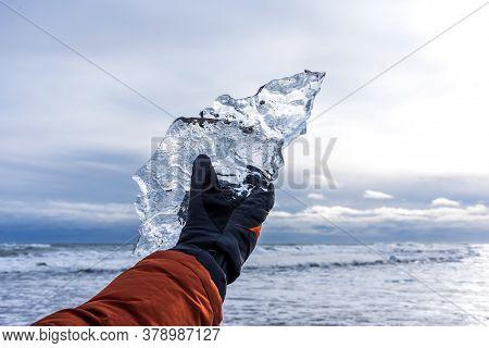 Male Hand Holds A Large Piece Of Ice On Diamond Beach Near Jokulsarlon Lagoon In Winter Time, Icelan