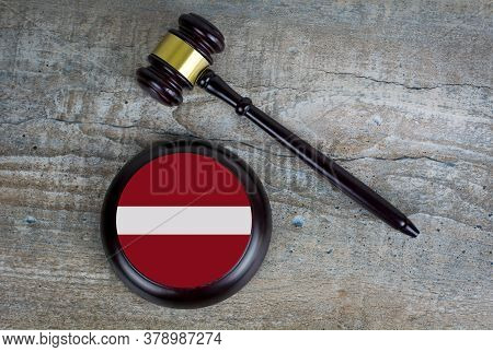 Wooden Judgement Or Auction Mallet With Of Latvia Flag. Conceptual Image.
