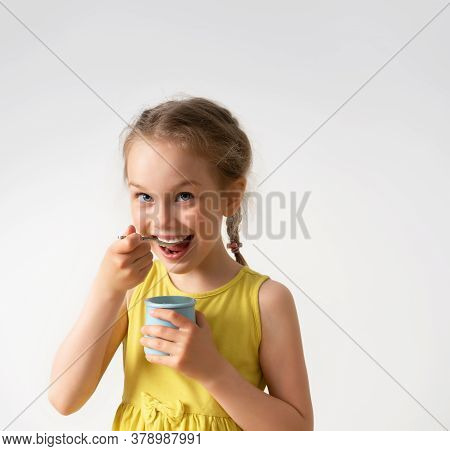 Charming Preschool Girl In Yellow Dress With Braided Hair Is Eating Yoghurt With Great Pleasure. Fac