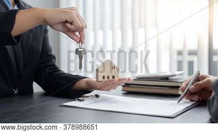 Sales manager or real estate agent holds the key handing it to the customer after signing the house