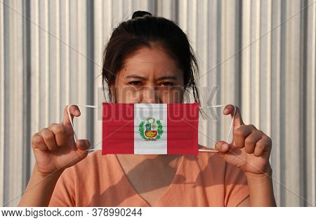 A Woman With Peru Flag On Hygienic Mask In Her Hand And Lifted Up The Front Face On Grey Background.