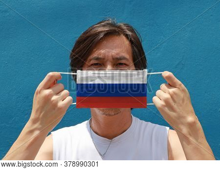 A Man With Russia Flag On Hygienic Mask In His Hand And Lifted Up The Front Face On Blue Background.