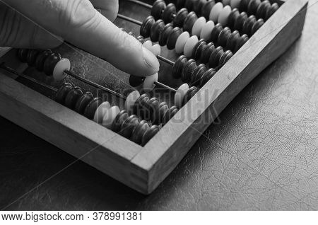 A Middle-aged Caucasian Man Makes Calculations On A Wooden Abacus. Close-up Of A Male Hand. An Obsol