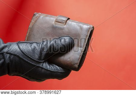 Hand In Black Leather Glove Holds Out Brown Wallet. Male Hand Holds Wallet To Pay For Purchase Or Th