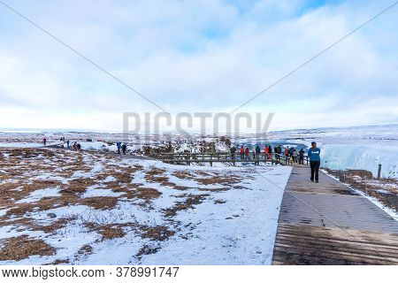 Gullfoss, Iceland - March 4, 2020: Tourists At Observation Deck Look At Gullfoss Waterfall. People A
