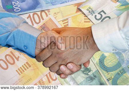Handshake Of Two Hands Men Closeup On Background Of Israeli Money Banknotes. Handshake Over New Isra