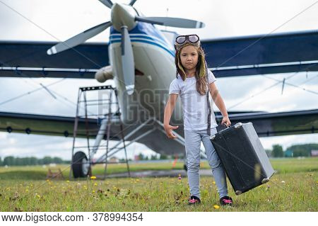 A Little Girl In A Pilots Costume Carries A Retro Suitcase And Walks Along The Airfield. A Child In