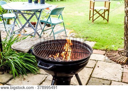 Bbq Grill With Flames In An Empty Back Garden Preparing To Cook Outside