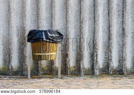 Wooden Trash Bin On Gray Concrete Wall Background