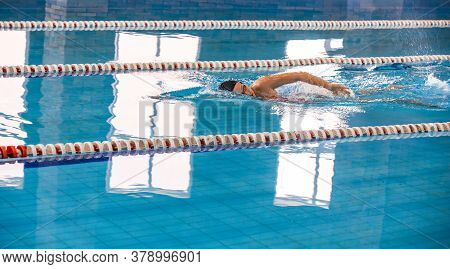 Young Woman Swimmer Is Swimming In The Pool. Freestyle Stroke, Front Crawl Stroke. Swimming In Blue