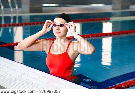 Portrait Of A Professional Swimmer Wearing Swimming Goggles And A Swim Cap, Resting In The Pool. Wom
