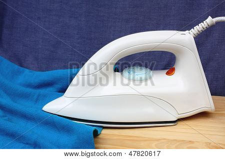 Electric iron and shirt on white and blue background