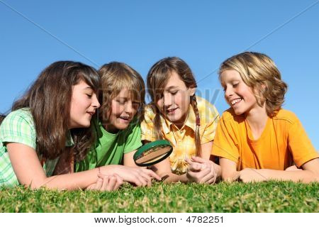 Group Of Kids Playing With Magnifying Glass