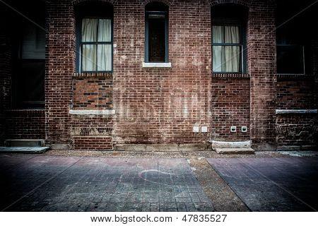 Old brick alleyway with brick walkway, doors and concrete stairs