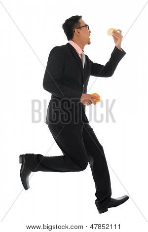 Full body Asian businessman in hurry eating bun and running, isolated on white background
