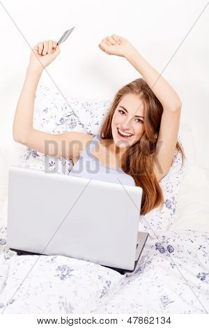 Girl Sitting In Bed And Shopping Online With Credit Card