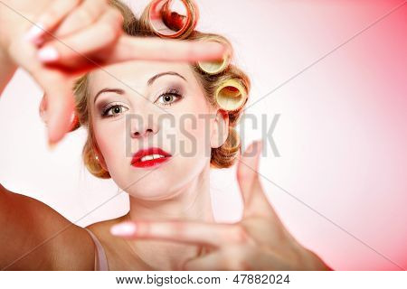Sexy woman preparing to party girl in underwear curlers in hair having fun making frame with hands taking picture with imaginary camera pink background poster