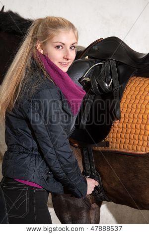 Girl Saddles Her Horse