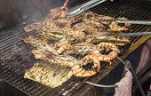 Prawns being cookoed on a grill outside a restaurant in Hua Hin Thailand poster