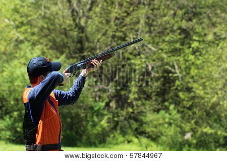 Young man skeet shooting